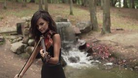 Muchacha hermosa en el vestido que toca el violín en bosque con la cascada en el fondo metrajes