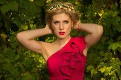 Muchacha hermosa en el vestido rojo que presenta en bosque Imagen de archivo libre de regalías