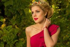 Muchacha hermosa en el vestido rojo que presenta en un fondo de hojas Imágenes de archivo libres de regalías