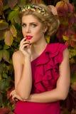 Muchacha hermosa en el vestido rojo que presenta en un fondo de hojas Fotografía de archivo