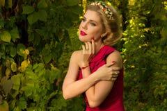Muchacha hermosa en el vestido rojo que presenta en un fondo de hojas Foto de archivo libre de regalías