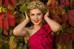 Muchacha hermosa en el vestido rojo que presenta en un fondo de hojas Foto de archivo