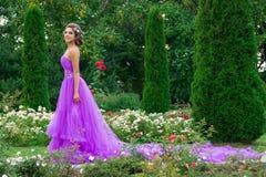 Muchacha hermosa en el vestido violeta entre en el jardín Imagen de archivo