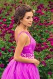 Muchacha hermosa en el vestido violeta entre en el jardín Foto de archivo libre de regalías