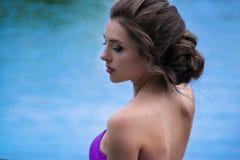 Muchacha hermosa en el vestido violeta entre en el jardín Imágenes de archivo libres de regalías