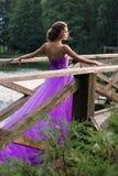 Muchacha hermosa en el vestido violeta entre en el jardín Fotografía de archivo libre de regalías