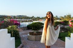 Muchacha hermosa en el vestido y las gafas de sol blancos Mujer feliz que sonríe y que mira el sol Día de verano soleado debajo d Imagenes de archivo