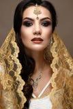 Muchacha hermosa en estilo indio con una bufanda en su cabeza Modelo con un maquillaje creativo y brillante Imagenes de archivo