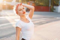 Muchacha hermosa en estilo retro con labios rojos y un vendaje en hea Imágenes de archivo libres de regalías