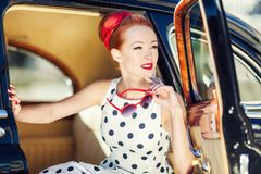 Muchacha hermosa en estilo retro y un coche del vintage Imagen de archivo