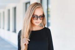 Muchacha hermosa en gafas de sol en el fondo de ventanas Fotografía de archivo