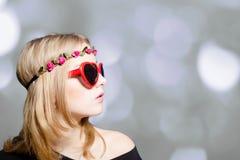 Muchacha hermosa en gafas de sol en forma de corazón en bokeh Imagenes de archivo