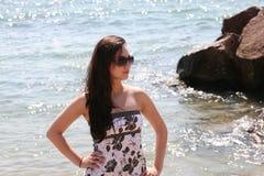 Muchacha hermosa en gafas de sol por el agua Foto de archivo libre de regalías
