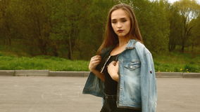 Muchacha hermosa en guiños y actitud de la chaqueta de los vaqueros Pelos del vuelo outdoor metrajes