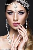 Muchacha hermosa en imagen de la novia árabe con joyería costosa, maquillaje oriental y la manicura nupcial Cara de la belleza Foto de archivo