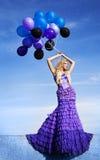 Muchacha hermosa en la alineada púrpura con los globos Imagenes de archivo