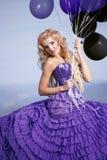 Muchacha hermosa en la alineada púrpura con los globos Fotografía de archivo