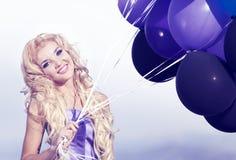 Muchacha hermosa en la alineada púrpura con los globos Fotos de archivo