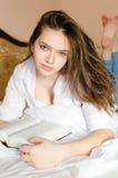 Muchacha hermosa en la camisa blanca que miente en la lectura de la cama Fotos de archivo