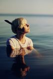 Muchacha hermosa en la camisa blanca que presenta en el agua en la puesta del sol Imagen de archivo