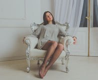 Muchacha hermosa en la camisa que se sienta en una silla del vintage Imagen de archivo