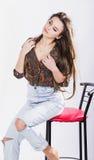 Muchacha hermosa en la camisa que se sienta en una trona contra un fondo blanco caliente El viento en su pelo sonrisas Foto de archivo libre de regalías