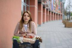 Muchacha hermosa en la carretilla cerca del supermercado outdoor fotografía de archivo