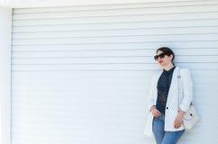 Muchacha hermosa en la chaqueta blanca y vaqueros en el fondo blanco de la pared de la puerta del garaje Verano casual de moda de imagenes de archivo