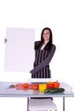 Muchacha hermosa en la cocina que lleva a cabo una muestra en blanco Fotografía de archivo libre de regalías
