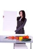 Muchacha hermosa en la cocina que lleva a cabo una muestra en blanco Imagenes de archivo