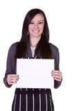 Muchacha hermosa en la cocina que lleva a cabo una muestra en blanco Imagen de archivo libre de regalías