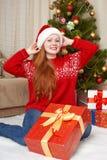 Muchacha hermosa en la decoración de la Navidad Interior del hogar con el árbol y los regalos adornados de abeto Noche Vieja y co Imágenes de archivo libres de regalías