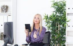 Muchacha hermosa en la oficina en el ordenador con el lector un pulgar para arriba Fotos de archivo libres de regalías