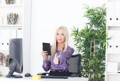 Muchacha hermosa en la oficina en el ordenador con el lector un pulgar para arriba Foto de archivo libre de regalías