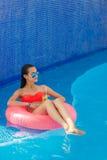 Muchacha hermosa en la piscina en salvavidas inflable imagenes de archivo