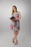 Muchacha hermosa en la presentación rosada con un libro, señora del negocio Imagen de archivo libre de regalías