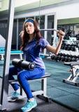 Muchacha hermosa en la ropa de deportes que hace ejercicio con un peso pesado Fotos de archivo libres de regalías
