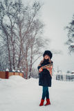 Muchacha hermosa en la ropa del invierno, capa y sombrero, presentando cerca de Foto de archivo