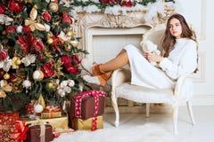 Muchacha hermosa en la silla cerca del árbol de navidad y de la chimenea Año Nuevo, imagen entonada, el proceso del ` s del autor Imagen de archivo libre de regalías