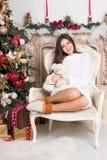 Muchacha hermosa en la silla cerca del árbol de navidad y de la chimenea Año Nuevo, imagen entonada, el proceso del ` s del autor Imágenes de archivo libres de regalías