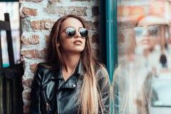 Muchacha hermosa en las gafas de sol que presentan en cámara Foto de archivo libre de regalías