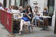 Muchacha hermosa en las gafas de sol que se sientan en una tabla en un café que mira el teléfono imágenes de archivo libres de regalías