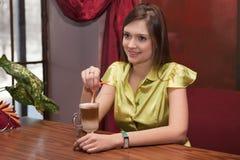 Muchacha hermosa en latte de consumición del restaurante Imágenes de archivo libres de regalías