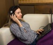 Muchacha hermosa en los auriculares que se sientan en un sofá en su ordenador portátil de las rodillas Imagen de archivo libre de regalías