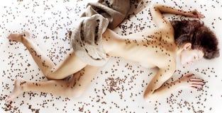 Muchacha hermosa en los granos de café Imagenes de archivo