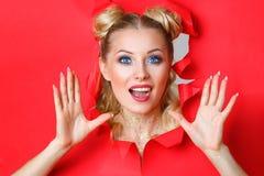 Muchacha hermosa en píos fuera del agujero en papel rojo, maquillaje brillante hermoso, expresiones faciales de la sorpresa e int foto de archivo