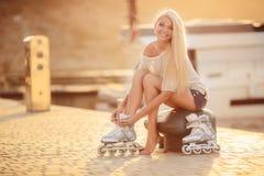 Muchacha hermosa en pcteres de ruedas en el parque Foto de archivo libre de regalías