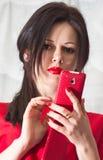 Muchacha hermosa en rojo con un teléfono brillante imagen de archivo
