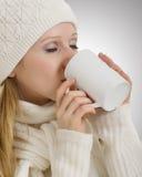 Muchacha hermosa en ropa del invierno que bebe la bebida Foto de archivo libre de regalías