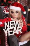 Muchacha hermosa en ropa y el sombrero caseros acogedores de Papá Noel que celebra el Ne Fotos de archivo libres de regalías